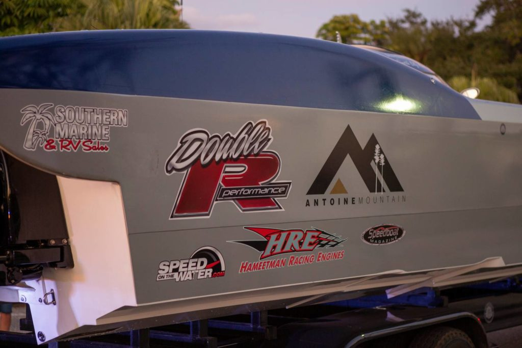 side of boat with various logos